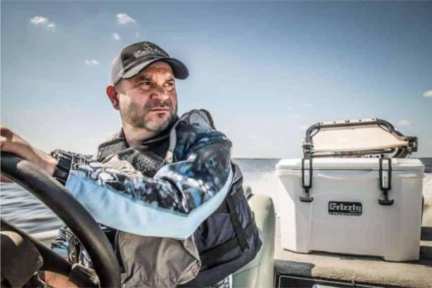 man driving boat with white grizzly 20 quart cooler