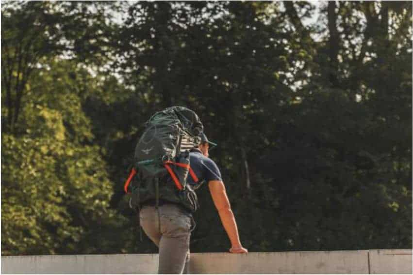 man with hiking backpack looking over bridge