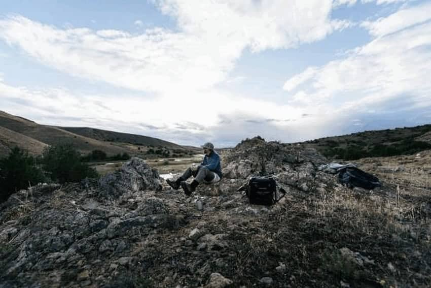 man enjoying nature, sitting next to a soft sided cooler with rolling hills in background