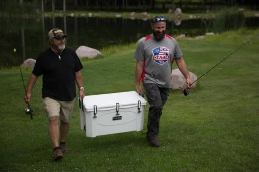 two fisherman carrying a white grizzly 100 rotomolded cooler away from a lake