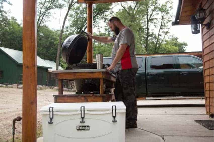 100 qt rotomolded cooler next to a man grilling