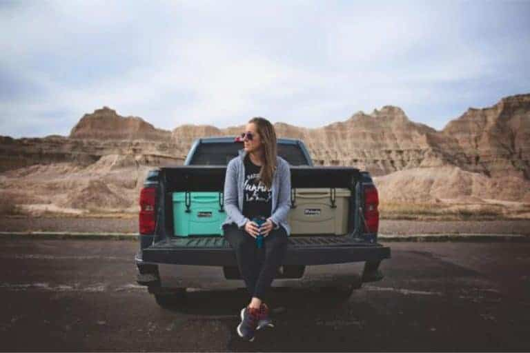 women sitting on tailgate of pickup truck with two 20 quart rotomolded coolers