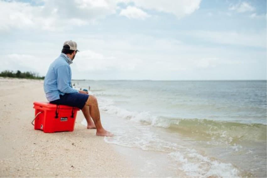 man sitting on red camping cooler on beach
