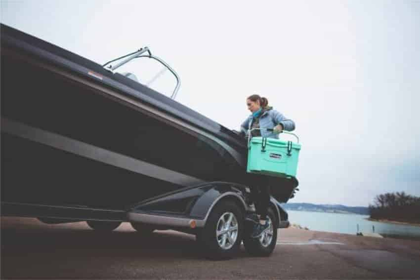 woman removing grizzly 20 cooler from boat near boat launch