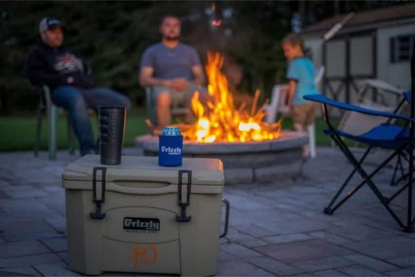 grizzly 20 quart cooler at campsite with camp fire in background