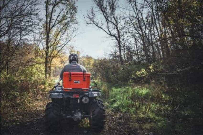 orange grizzly 20 cooler strapped to back of ATV vehicle on a trail