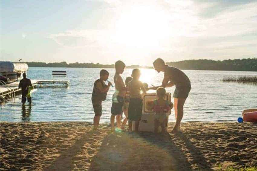 beverage cooler on beach surrounded by children