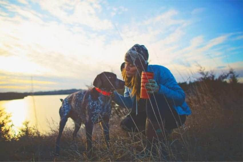 women holding red 20 oz stainless steel cup kneeling next to dog with lake in background