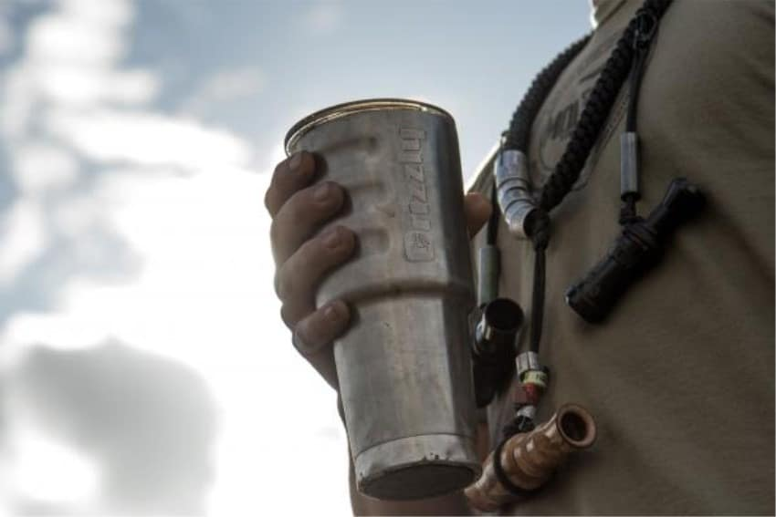 close up of person holding a 32 oz stainless steel cup with sky in background