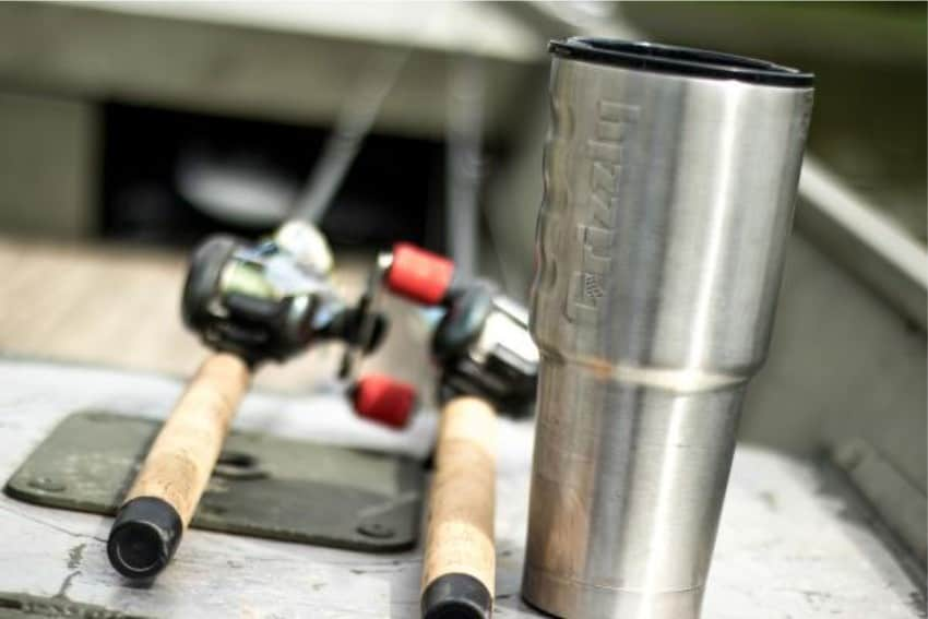 32 oz grizzly grip cup with baitcaster fishing rods in background