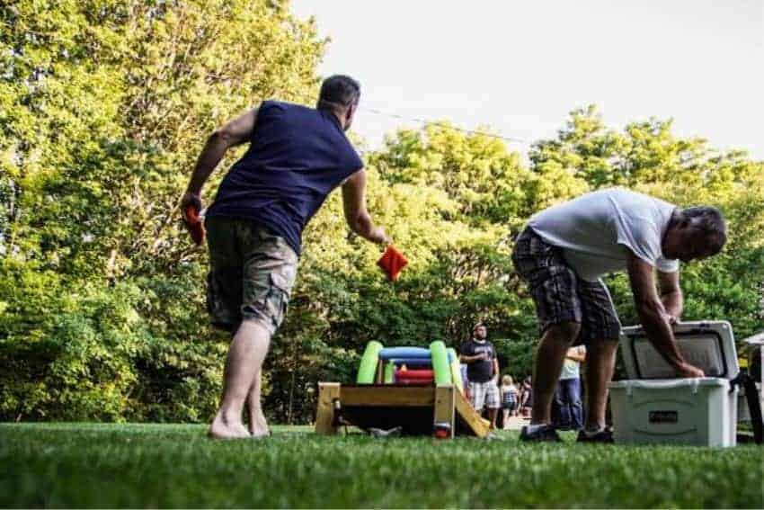man tossing bean bag while other man pulling a beverage out of a grizzly 20 cooler