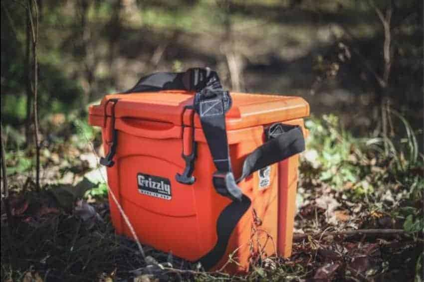 orange 15 qt cooler with carry strap sitting on hiking trail