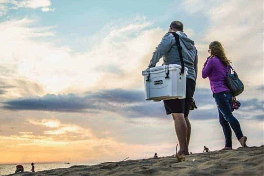 man and woman standing on beach looking into ocean with white grizzly 15 cooler