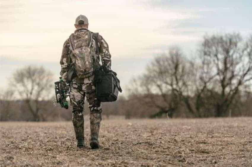 hunter walking into field with grizzly cooler bag over shoulder