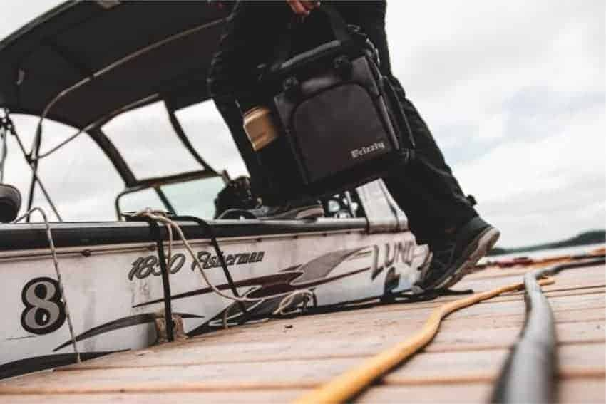 drifter 12+ soft sided cooler bag being carried onto boat with grip bottle in cooler pocket