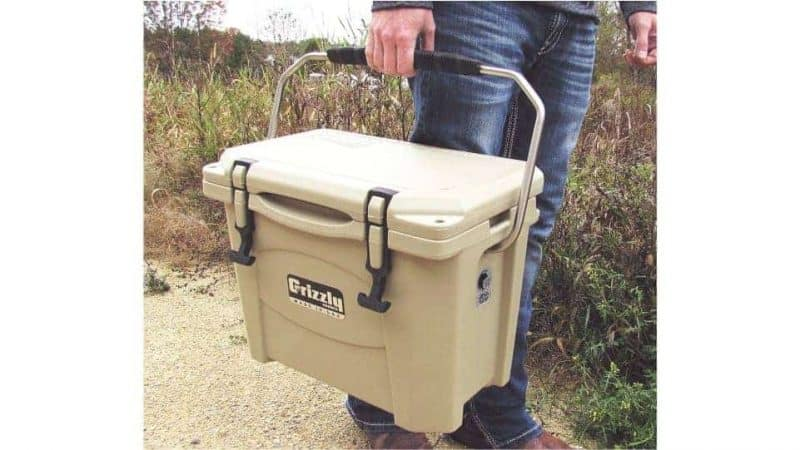 man holding grizzly 15 cooler with stainless steel handle