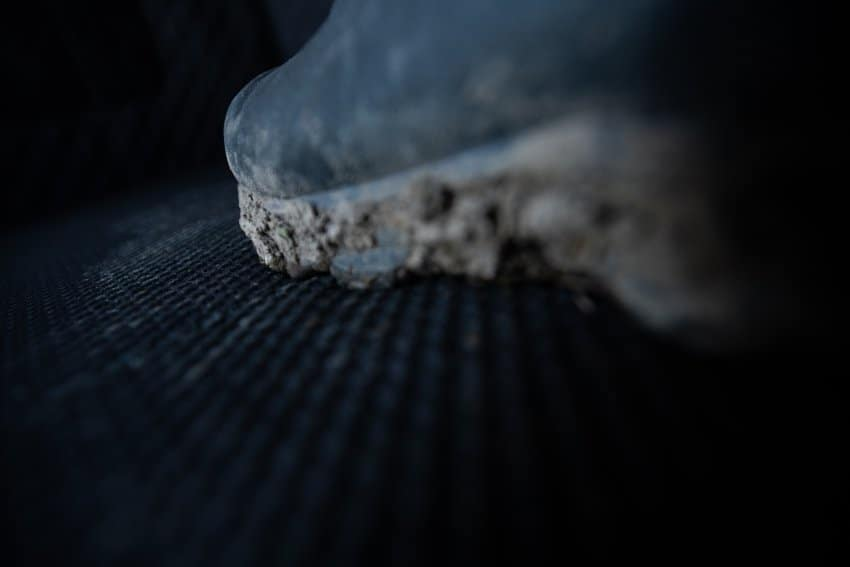 detailed view of hunting blind floor mat with muddy boot standing on it
