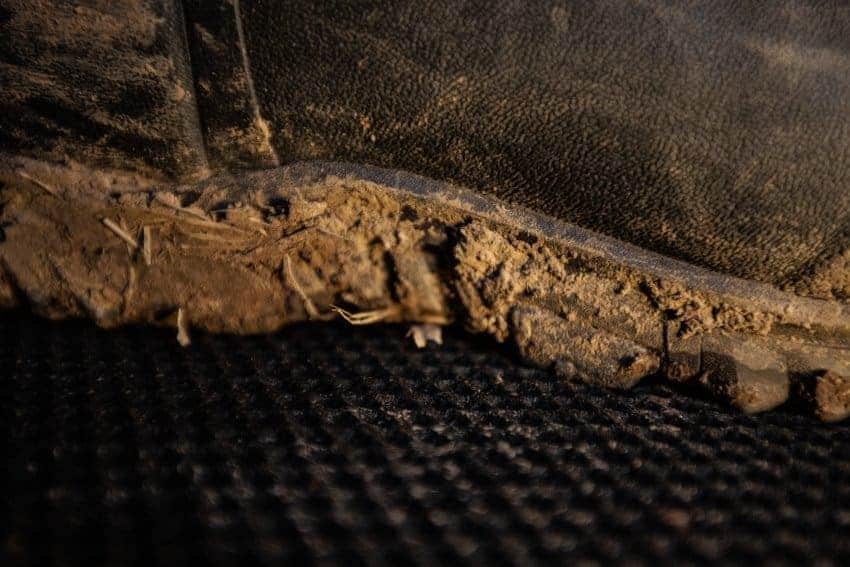 detailed view with sunlight of hunting blind floor mat with muddy boot standing on it