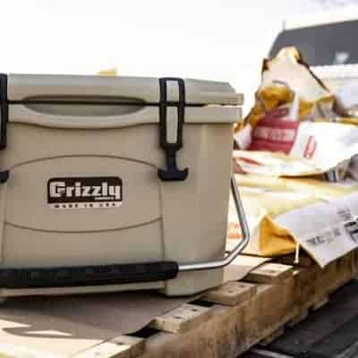 american farmer using a tan grizzly 20 cooler sitting on pallet in back of truck surrounded by corn seed bags