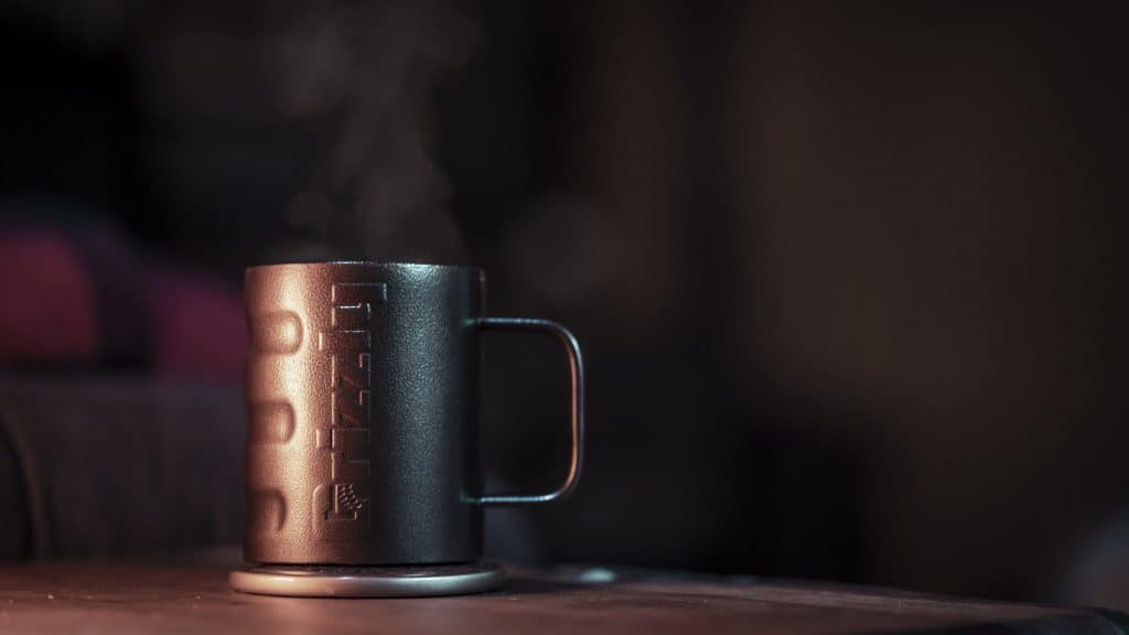 Grizzly Grip Camp Cup In Textured Copper Finish Sitting On Table With Steam Coming Out Of Coffee Cup