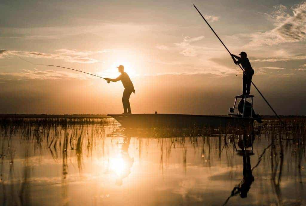 silhouettes of fisherman casting from a boat with sun-setting in background