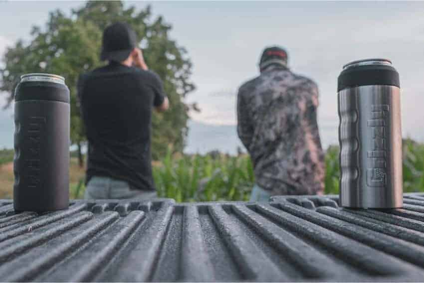 two slim can koozie sitting on edge of truck with two men standing looking into field
