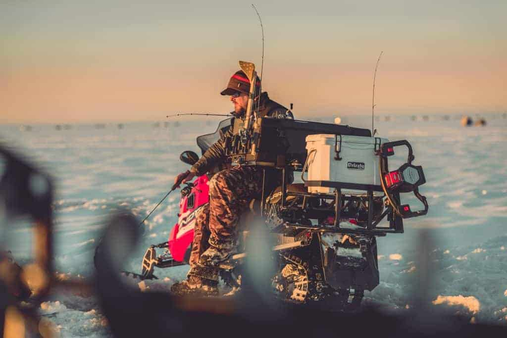 Pro Angler Matt Peters Giving Ice Fishing Tips While Sitting On Snow Mobile