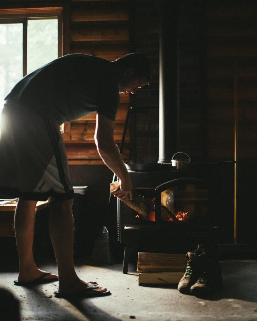 Man Stoking A Woodstove With Cast Iron Skillet Ontop Of Woodstove