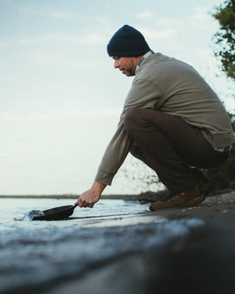 Man Cleaning Cast Iron Skillet In Lake