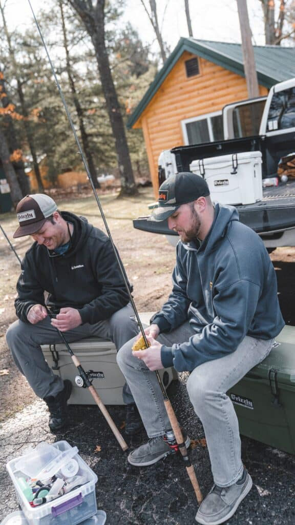 Steelhead Anglers Sitting On Grizzly Coolers At Camp