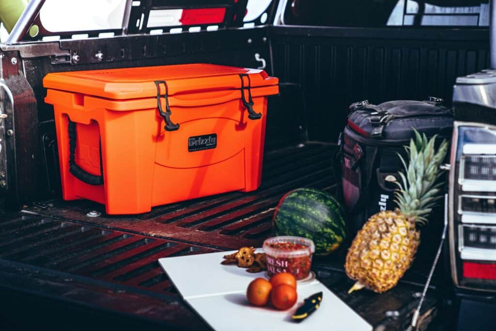 Orange Grizzly Cooler In Back Of Truck With Meal Prep In Foreground