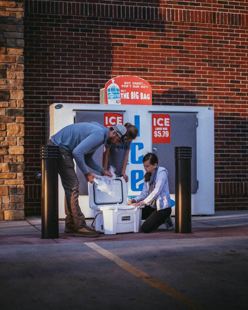 Man And Women Filling Ice In A Grizzly Cooler Outside A Ice Cooler