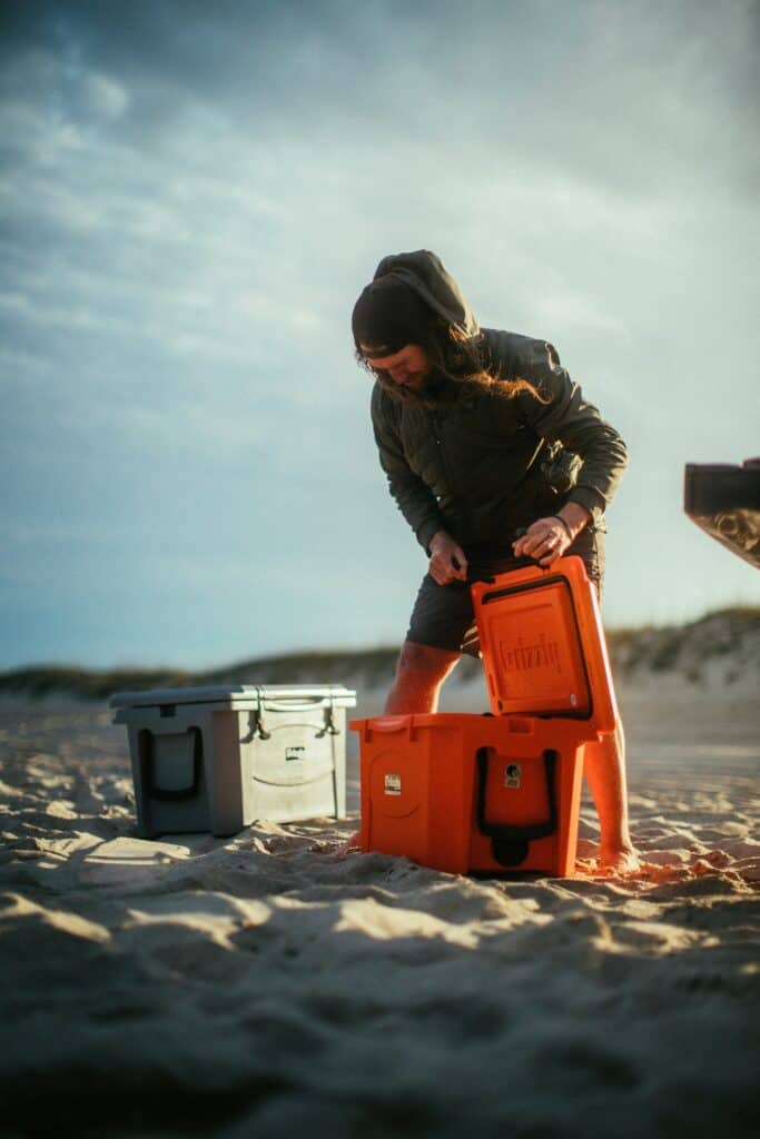 Man Opening A Grizzly Cooler At Music Festival On Beach