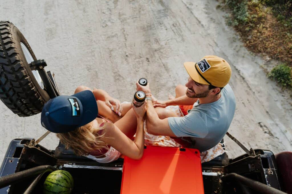 2 People Sitting On Tailgate At Summer Palooza Enjoying Refreshments While Using Grizzly Coolers Drinkware, Overhead Angled Shot