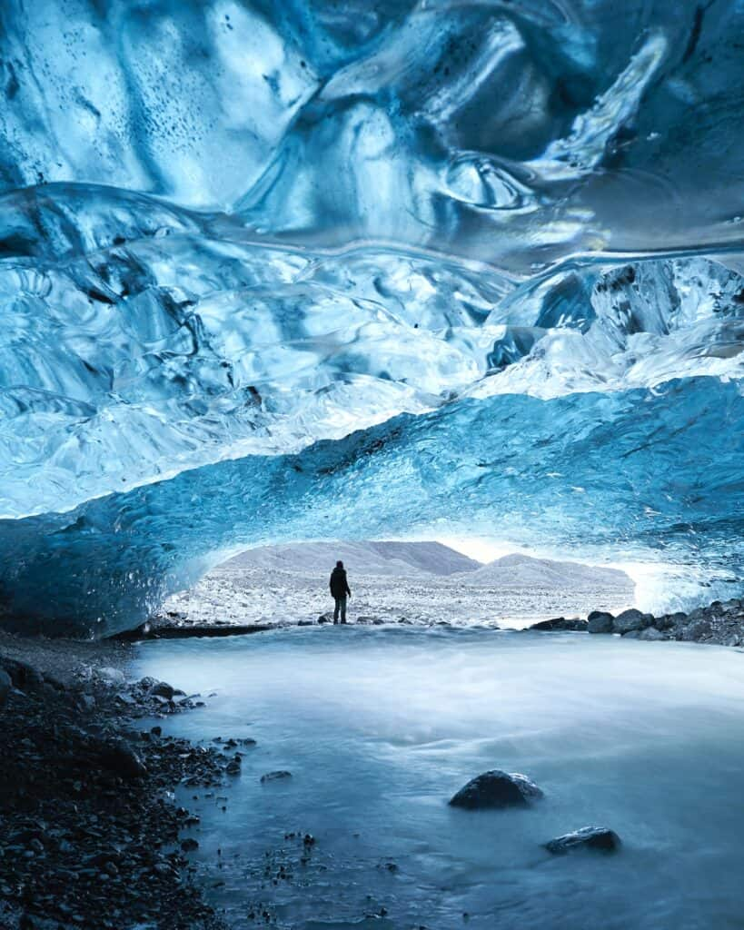 Man Standing At Opening Of Glacier Cave