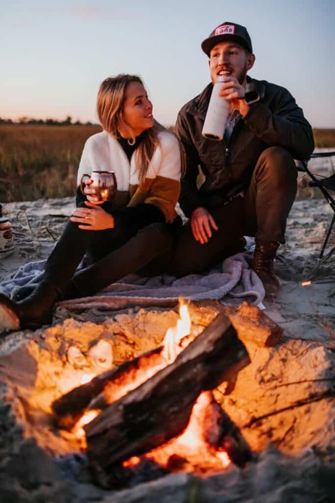 Man And Woman Enjoying A Campfire At Sunset