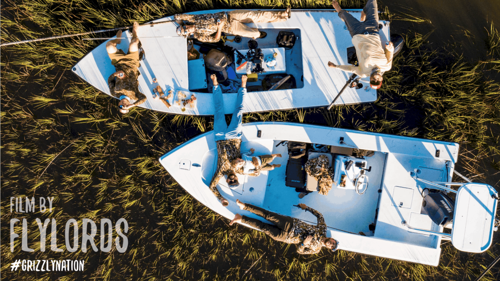 aerial view of two boats in tall grass with people laying on boats