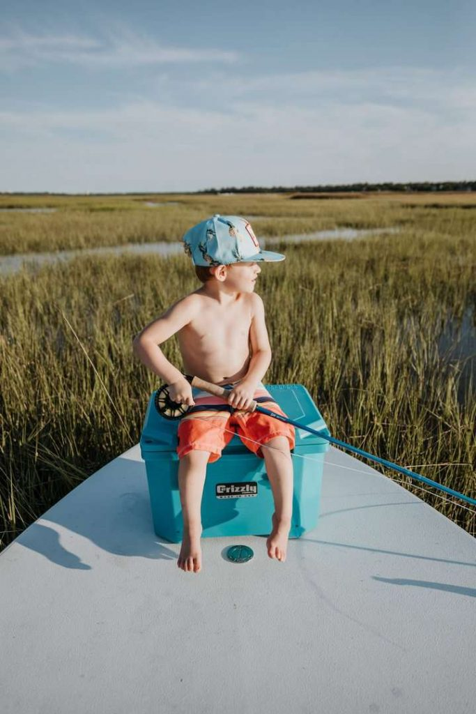 boy wearing a hat sitting on teal grizzly 20 cooler holding a fly fishing rod looking to the side