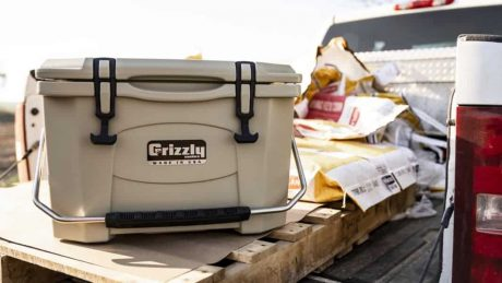 tan grizzly 20 cooler sitting on pallet in back of truck surrounded by corn seed bags