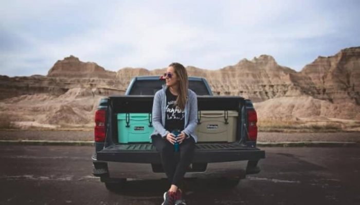 how to plan a road trip, women sitting on tailgate of pickup truck with two 20 quart rotomolded coolers