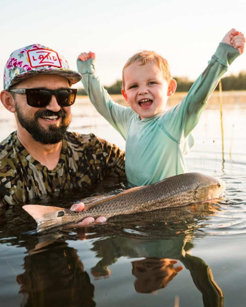 father and son standing in river holding Red fish