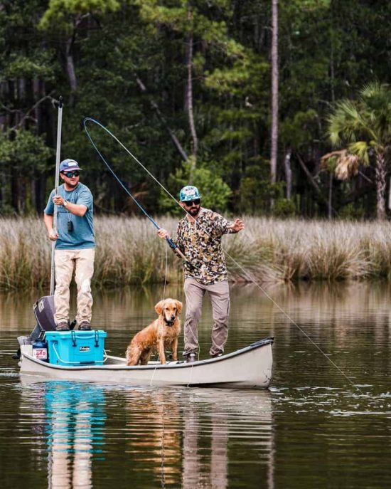 two men and dog on canoe fly fishing with grizzly hard sided cooler